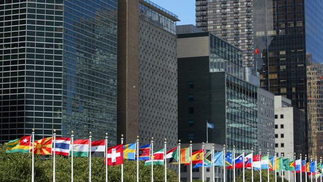 Le drapeau suisse flotte devant les bâtiments de l'ONU à New York en 2002. [Alessandro Della Valle - Keystone]