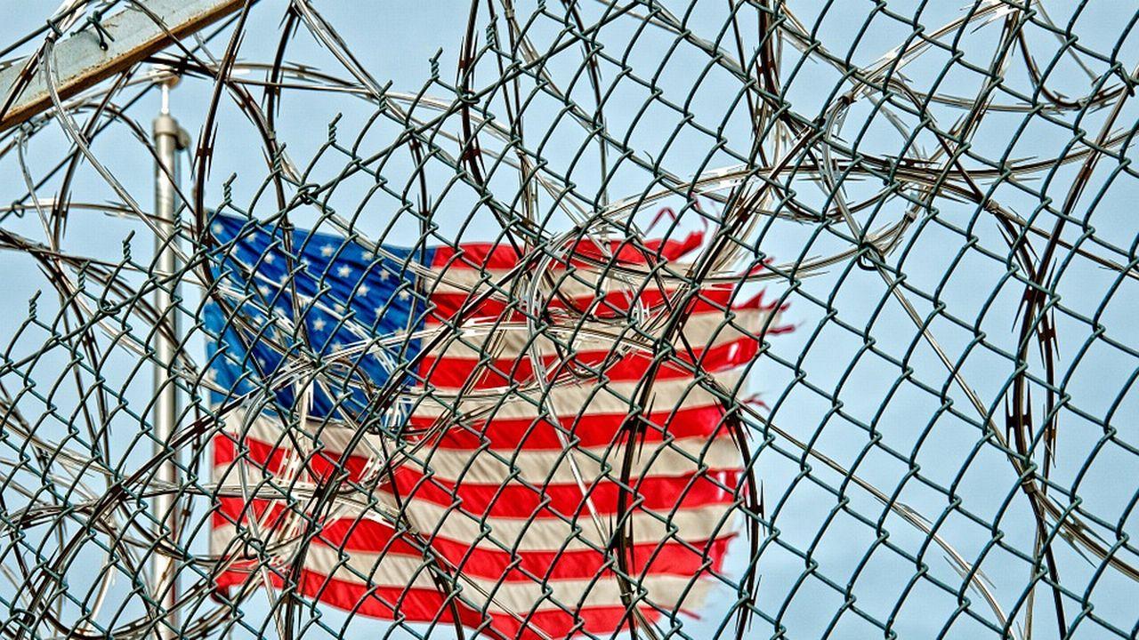 Un drapeau américain flottant derrière le grillage d'un pénitencier. [CC0 Creative Commons]