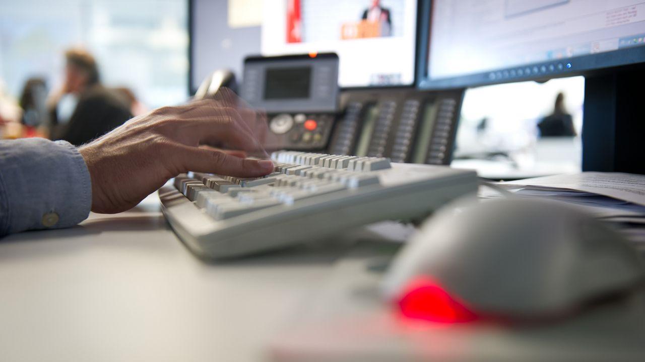Un homme devant un ordinateur dans un bureau. [Daniel Naupold - DPA/Keystone]