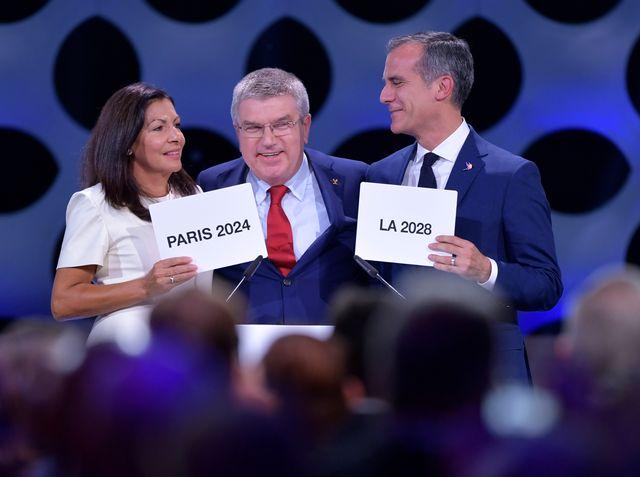 Comme à l'école des fans, tout le monde a gagné. Les maires de Paris (à gauche) et de Los Angeles (à droite) aux côtés du président du CIO Thomas Bach. [Fabrice Coffrini - AFP]