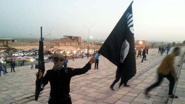 Un combattant du groupe Etat islamique brandit le drapeau de l'organisation dans les rues de Mossoul, 23 juin 2014. [STRINGER Iraq - Reuters]