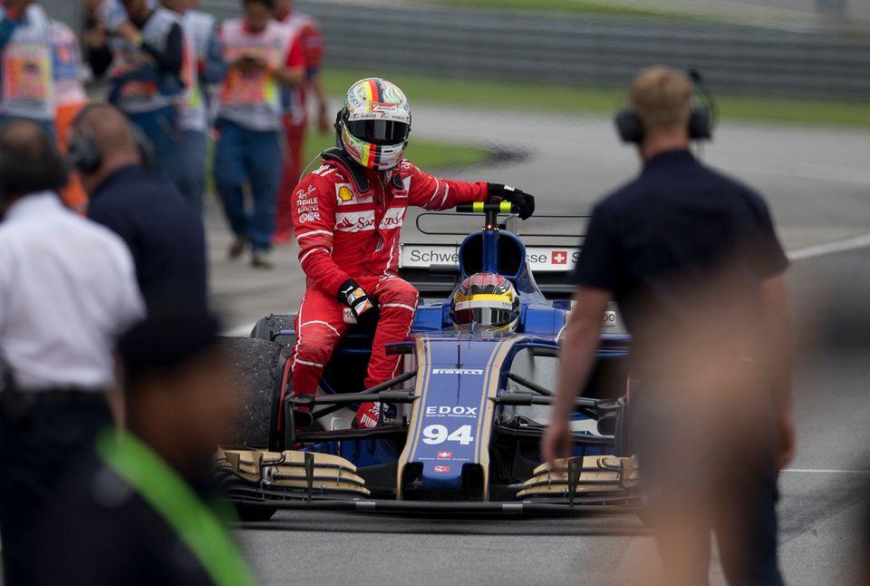 Sebastian Vettel (Ferrari) s'offre un petit tour sur la Sauber de Pascal Wehrlein. [Tomas Lam - Keystone]