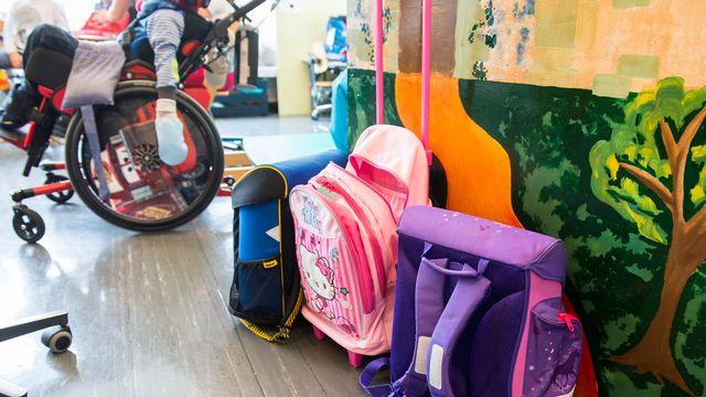 Un enfant handicapé et des cartables d'écoliers en classe (image d'illustration). [Dominic Steinmann - Keystone]