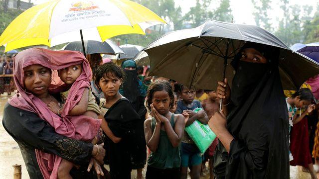 Les réfugiés Rohingya font la file d'attente sous la pluie pour recevoir des biens de première nécessité près d'un centre à Balukhali, au Bangladesh, le 12 octobre 2017 [ABIR ABDULLAH - KEYSTONE]