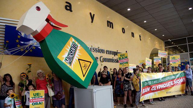 Des militants réclamant l'interdiction du glyphosate dans l'Union européenne font tomber symboliquement à terre une bouteille géante de Roundup, en juillet 2017 à Bruxelles. [Thierry Charlier - AFP]