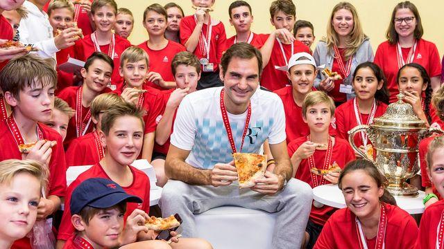 Roger Federer et les ramasseurs de balle avec la pizza tradition de fin de tournoi. [Alexandra Wey - Keystone]