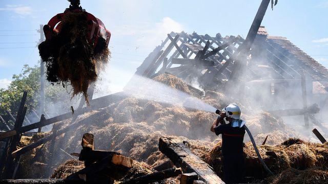 Des pompiers à l'oeuvre sur le site d'un incendie qui a complètement détruit une ferme, le 29 juillet 2017 à Payerne. [Christian Brun - Keystone]
