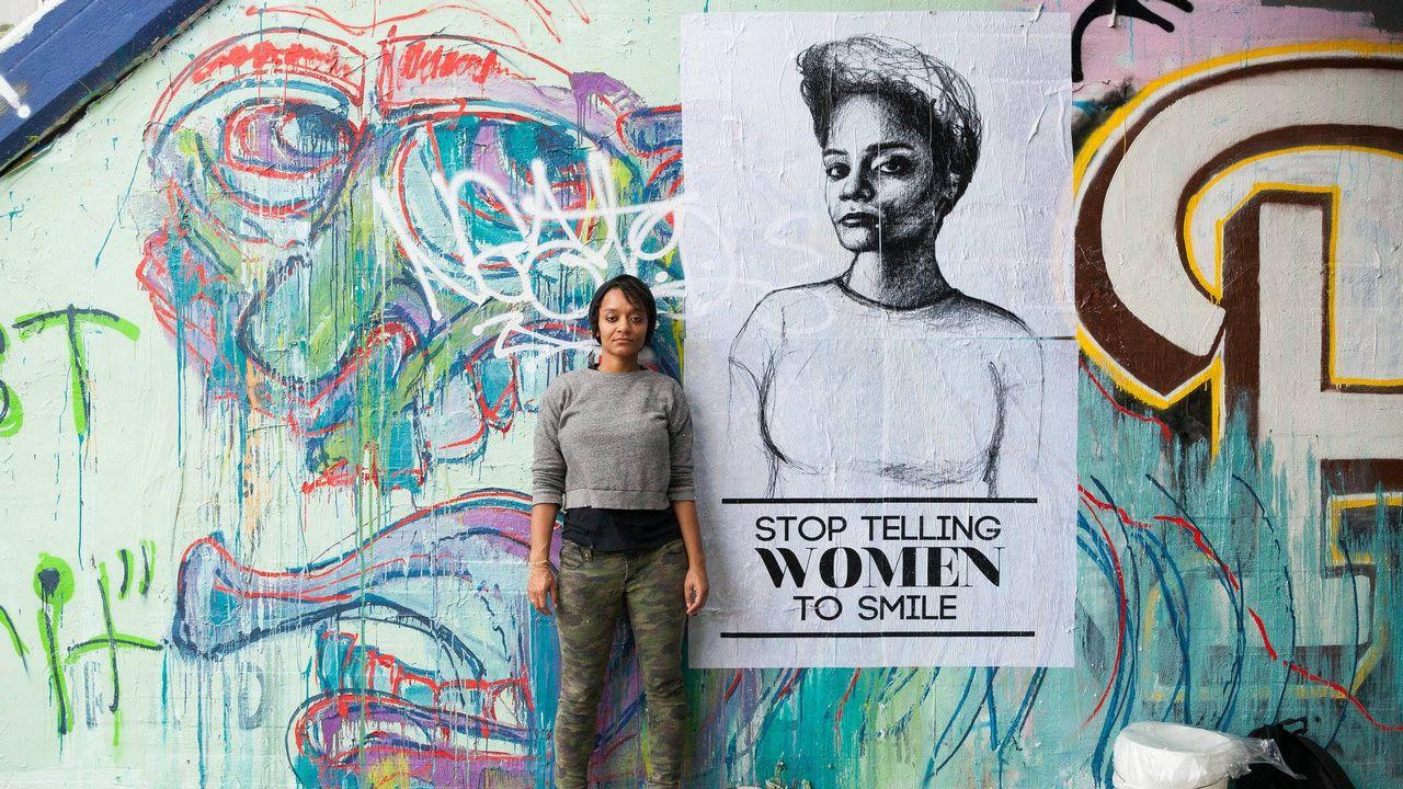 """Tatyana Fazlalizedeh devant un des portraits de la série """"Stop telling women to smile"""". [DR]"""