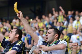 Un supporter brandit une banane alors que l'équipe de Galatasaray arrive. [Ozan Kose - AFP]