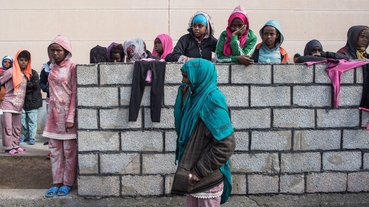 Une femme et des enfants attendant devant le centre pour migrants de Tariq Al-Matar, près de Tripoli. [Taha Jawashi - AFP]