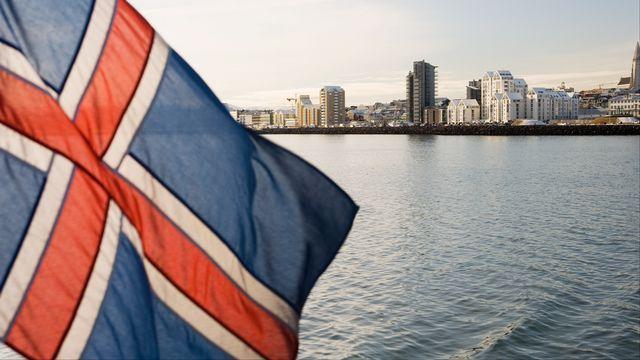 Un drapeau islandais flotte avec Reykjavik, la capitale du pays, en arrière-plan. [Stuart Westmorland - AFP]
