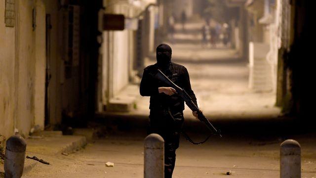 Un membre des forces spéciales tunisiennes patrouille dans un quartier de Tunis, avec des manifestants en arrière-plan. [FETHI BELAID - AFP]