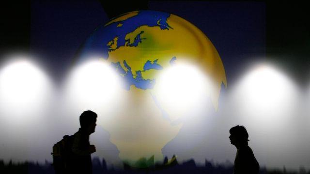 Des volontaires passent devant une carte du monde lors du World Economic Forum de Davos en janvier 2008. [Stefan Wermuth - Reuters]