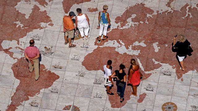 Des passants sur une grande carte du monde en marbre à Lisbonne, au Portugal. [Jose Manuel Ribeiro - Reuters]