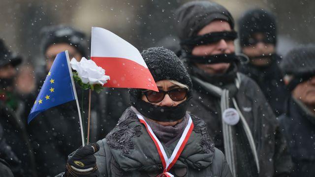 """Des membres de l'Opposition en Pologne protestent contre les décisions prises par le parti ultraconservateur """"Droits et Justice"""" dirigé par Jaroslaw Kaczynski. [ARTUR WIDAK / NURPHOTO - AFP]"""