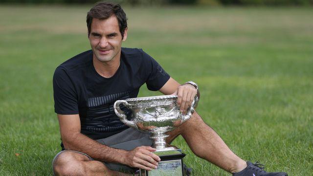 Federer pose tout sourire avec son trophée au lendemain de son sacre à Melbourne. [Dita Alangkara - Keystone]