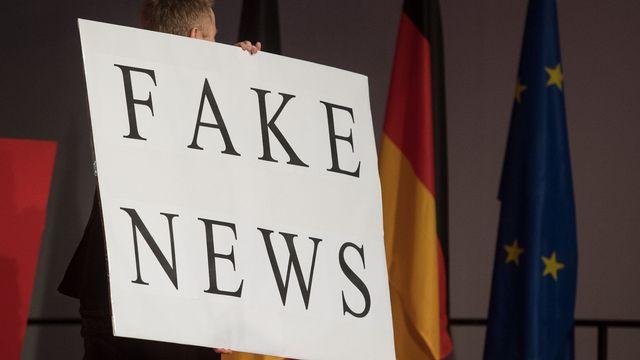 """Un homme porte un panneau """"Fake News"""" le 01.03.2017 à Fellbach, en Allemagne, lors d'un meeting de la CDU. [Marijan Murat - Keystone/DPA]"""