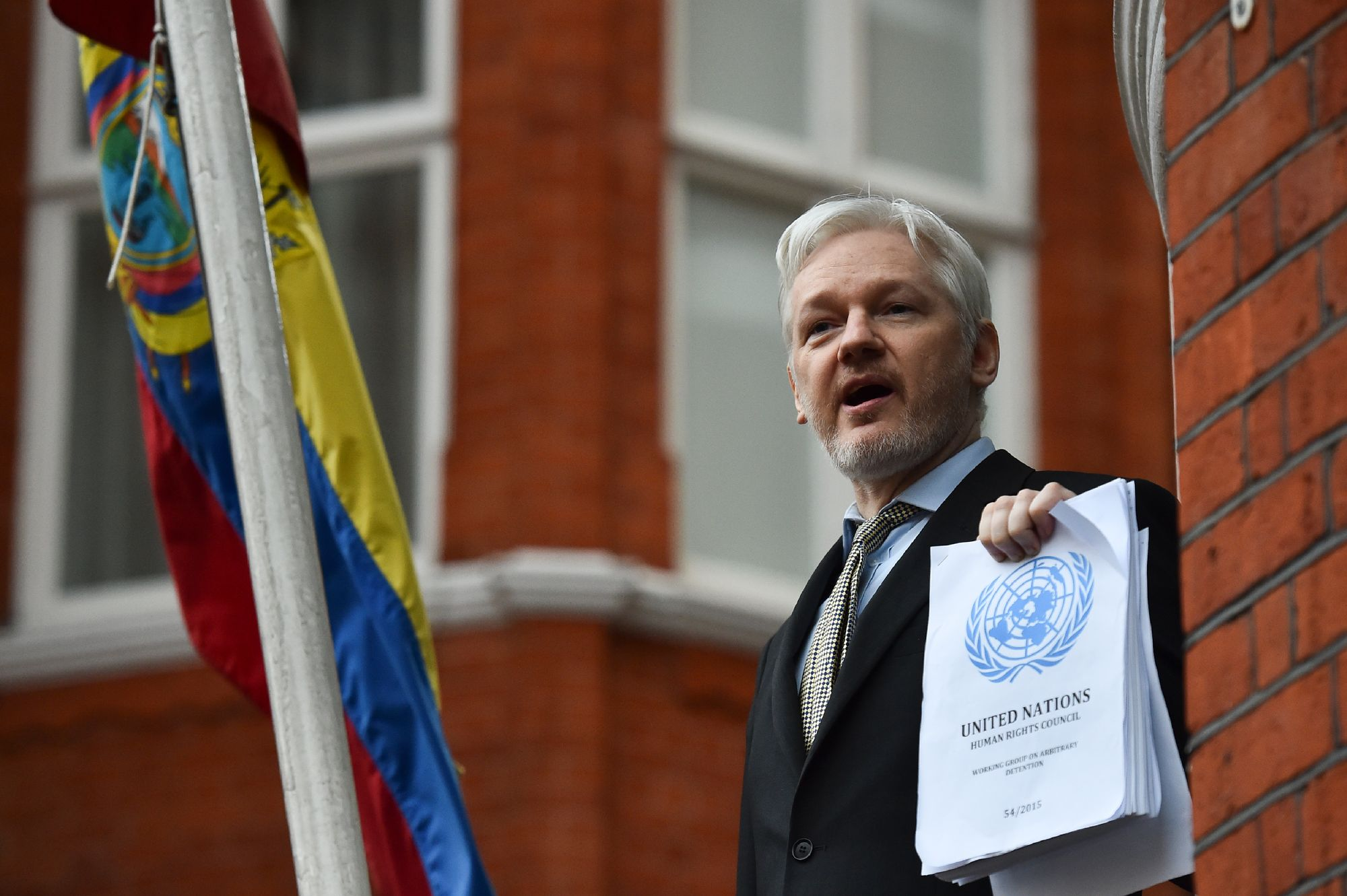 Julian Assange exhibe un document depuis l'ambassade de l'Equateur à Londres.
