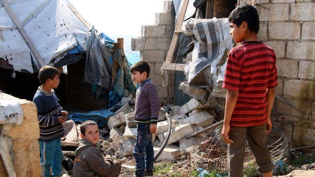Des enfants se tiennent près de décombres dans la ville syrienne d'Atma, dans la province d'Idleb (nord du pays), le 6 février 2018. [Aref Watad - EPA/Keystone]