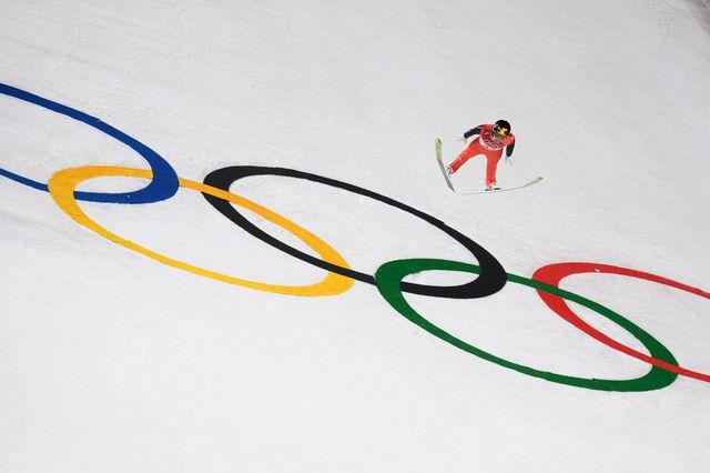 Simon Ammann vole au-dessus des anneaux olympiques à Alpensia. [Gian Ehrenzeller - Keystone]