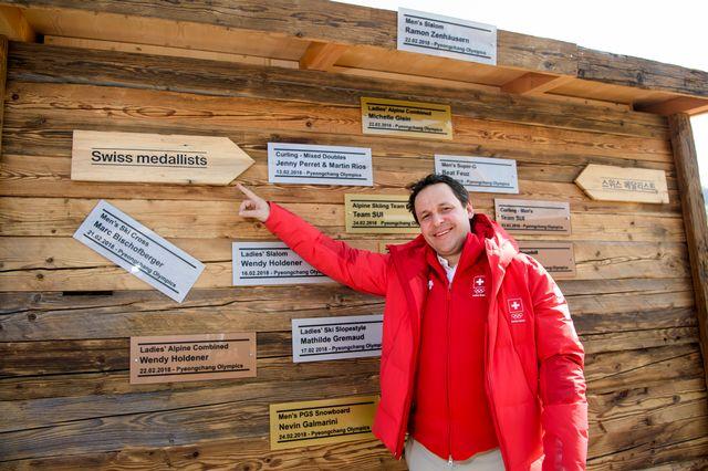 Ralph Stöckli pose dans la maison suisse, devant la paroi avec les médailles suisses [Jean-Christophe Bott - Keystone]