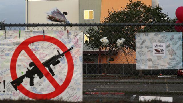 Une affiche anti-armes posée sur une barrière devant le lycée de Parkland après la tuerie. [Joe Raedle - Getty Images North America/AFP]