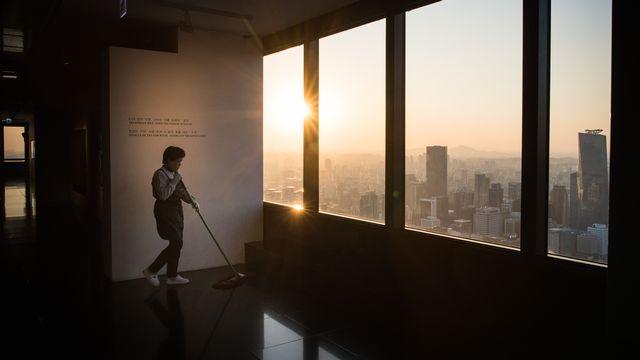 Une employée de nettoyage dans un gratte-ciel de la capitale sud-coréenne Séoul. [Ed Jones - AFP]