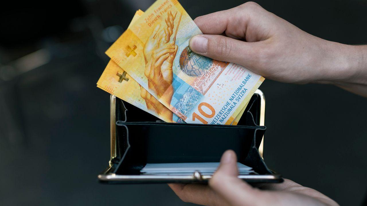 Trois billets de 10 francs, soit 30 francs, sortent d'un porte-monnaie. [Christian Beutler - KEYSTONE]