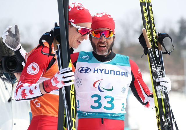 Brian McKeever avec son guide Graham Nishikawa après la victoire. [Yomiuri Shimbun - AFP]