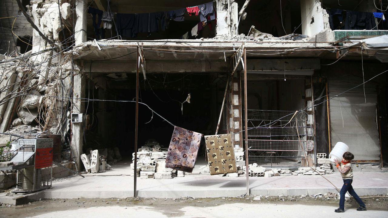 Un jeune garçon passe devant un immeuble éventré à la suite de bombardements. [Bassam Khabieh - Reuters]