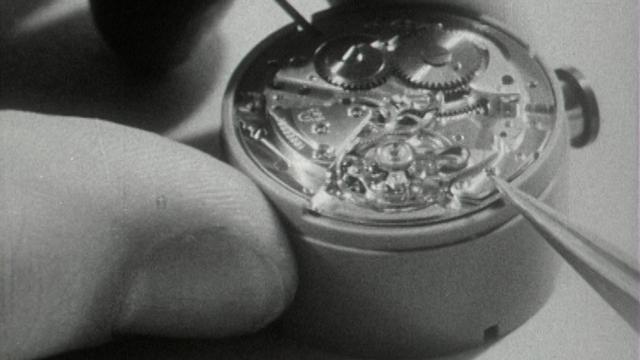 Horloger assemblant une montre en 1963. [RTS]