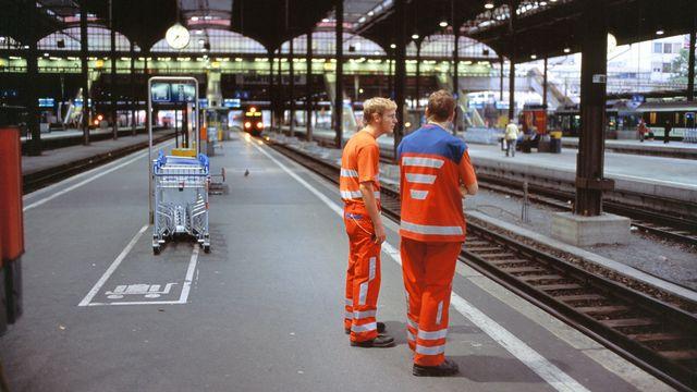 Des employés CFF sur un quai de la gare à Bâle. [Martin Rütschi - Keystone]