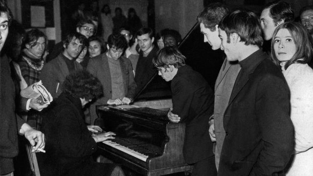 Un jeune homme joue du piano au milieu d'étudiants à l'université de la Sorbonne, à Paris, le 20 mai 1968. [Archives - AFP]