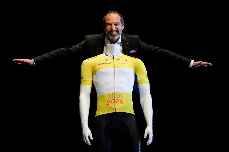 """Richard Chassot, directeur du Tour de Romandie, pose avec le maillot jaune """"Sion 2026"""". [Jean-Christophe Bott - Keystone]"""
