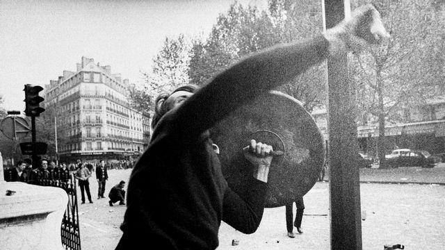 Manifestant lançant un pavé en direction de policiers en mai 1968. [AP/Keystone]