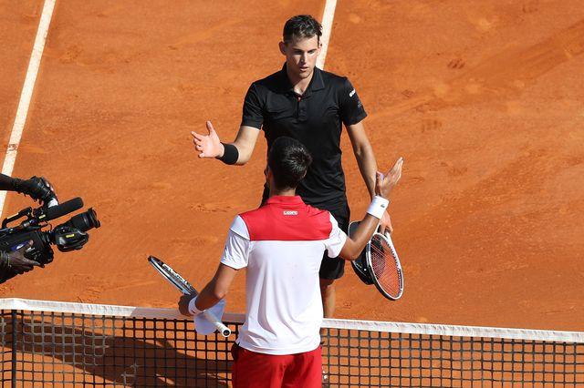 Djokovic (en blanc) a mordu la poussière face à Thiem. [Valery Hache - AFP]