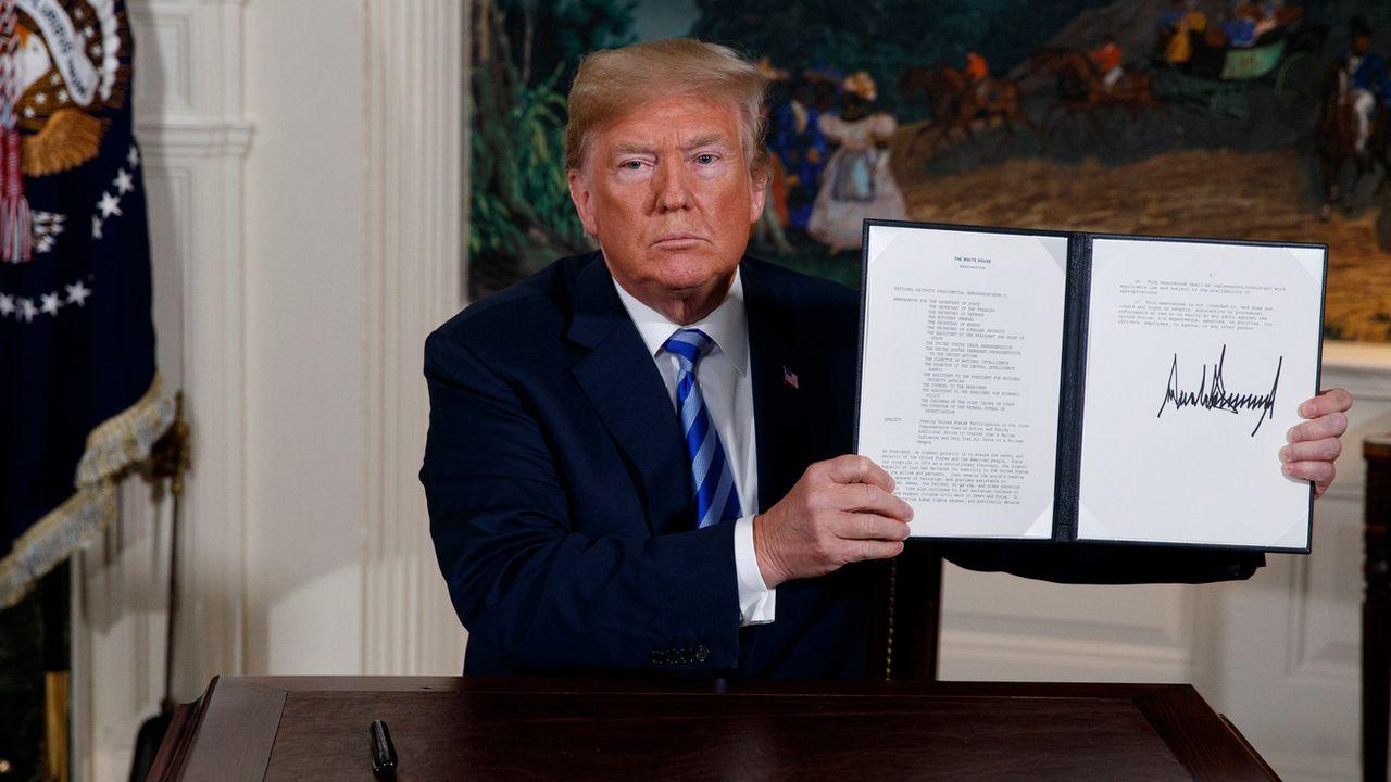 Le président américain Donald Trump montre la signature du document rétablissant les sanctions contre Téhéran. [Evan Vucci - Keystone]
