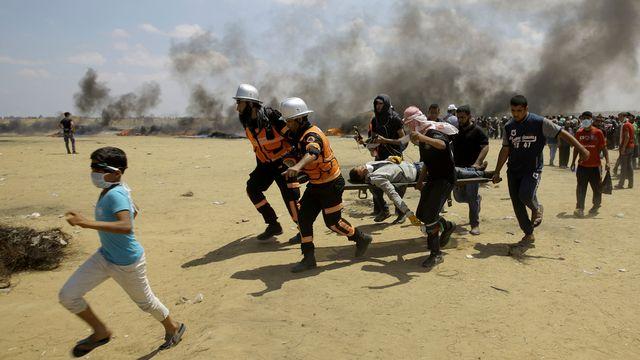 Evacuation d'un blessé durant une manifestation sanglante à la frontière de Gaza, lundi 14 mai, jour de l'inauguration de l'ambassade américaine à Jérusalem. [Keystone]