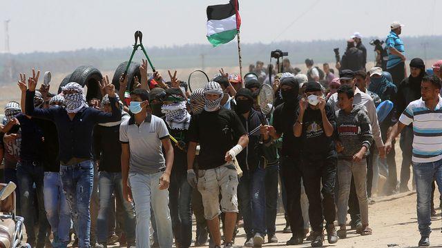 Des jeunes Palestiniens manifestent sur la frontière entre Israël et Gaza. [Adel Hana - Keystone]