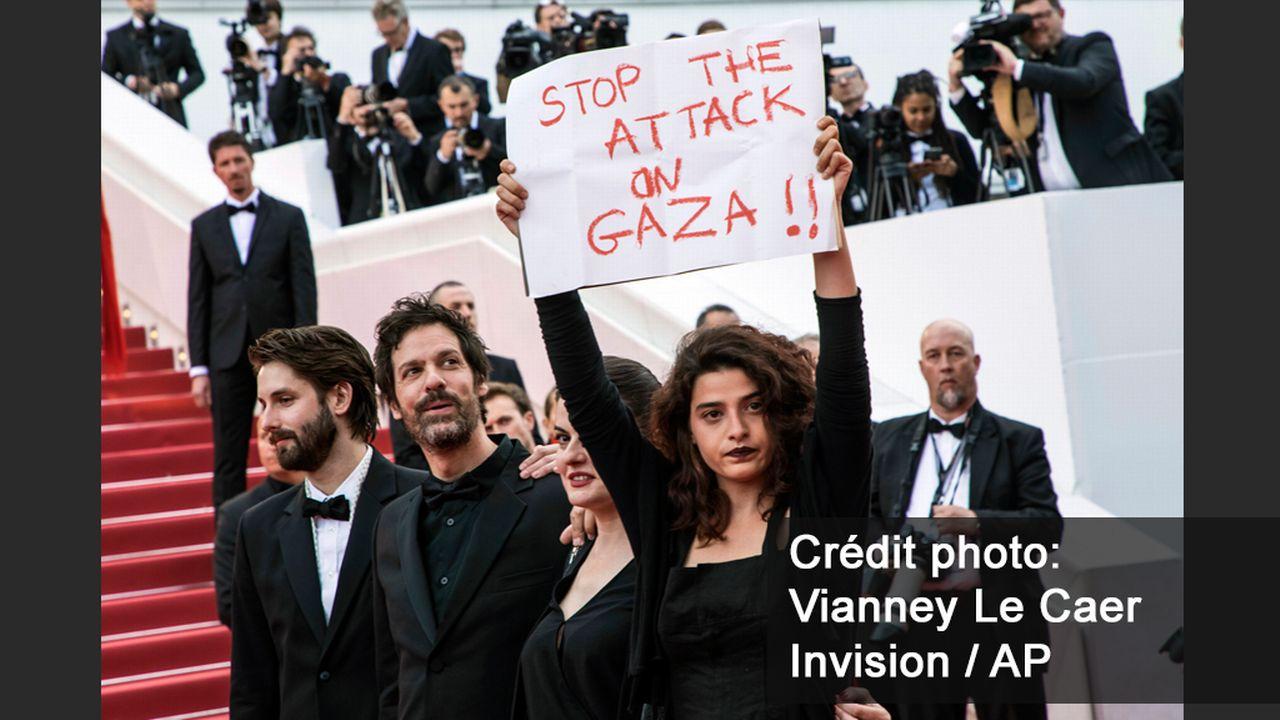 L'actrice Manal Issa a brandi cette affiche de soutien aux Palestiniens lors de la montée des marches. [Vianney Le Caer - Invision/AP]