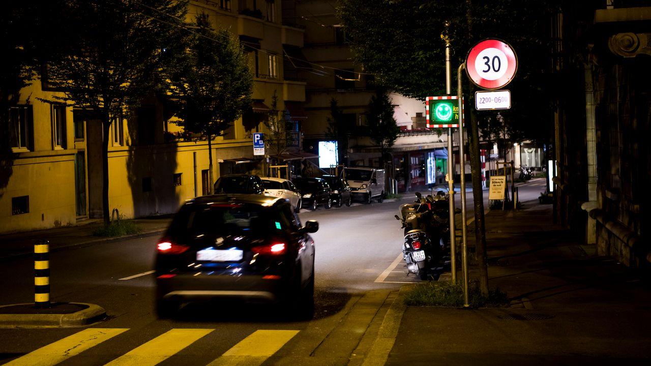 Une voiture roule de nuit à Lausanne. [Jean-Christophe Bott - Keystone]