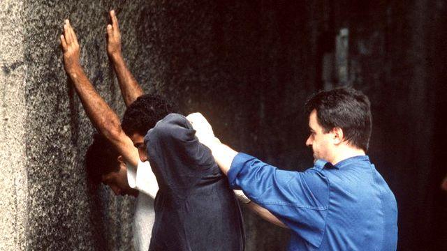 Un policier fouille des dealers présumés à Zurich en août 1994. [Martin Rütschi - Keystone]
