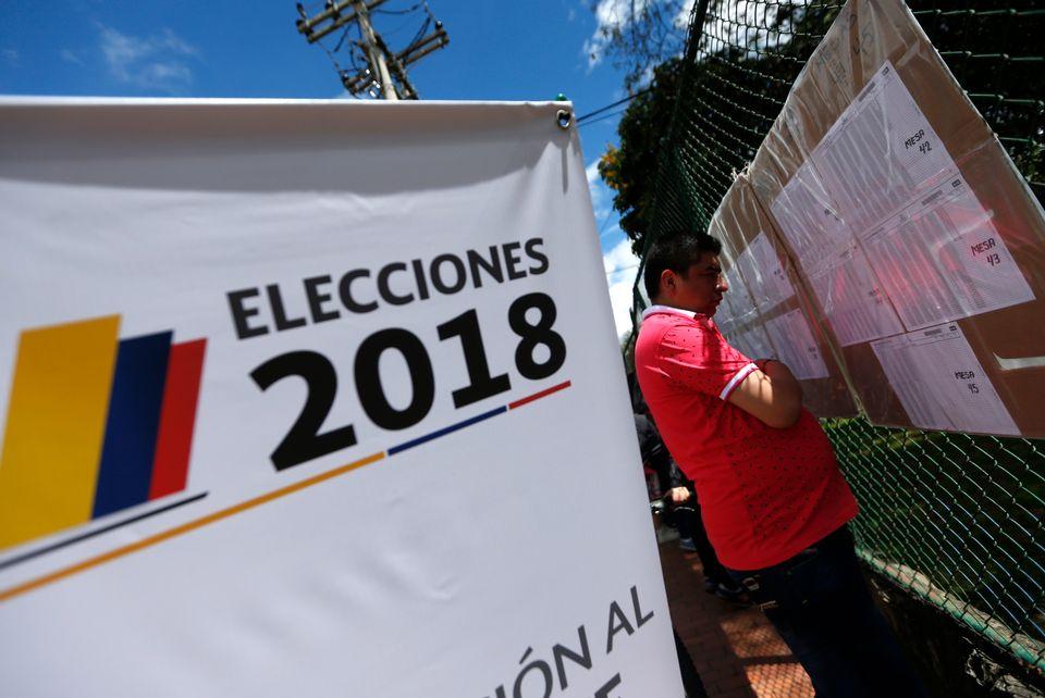 Un homme regarde les listes électorales lors du second tour de la présidentielle à Bogota, le 17 juin 2018. [Luisa Gonzalez - Reuters]