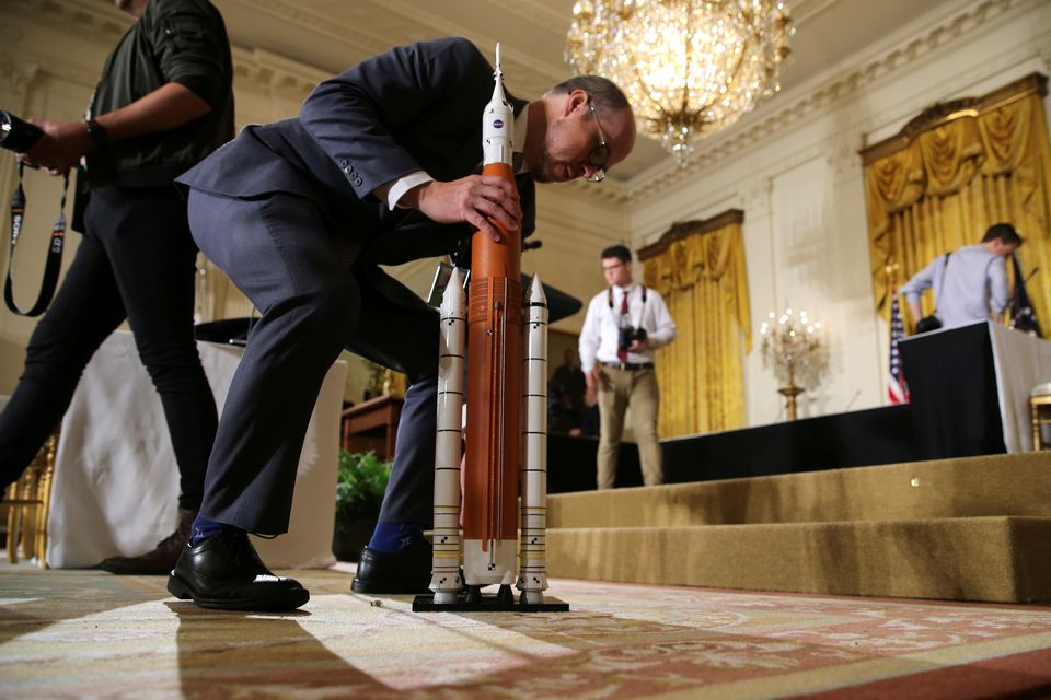 Un employé de la Maison Blanche installe la maquette d'une fusée avant l'intervention du président Donald Trump. [Jonathan Ernst - Reuters]