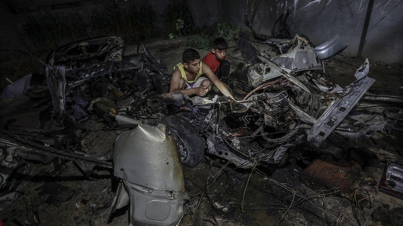 De jeunes Palestiniens inspectent les débris d'une voiture détruite par des raids aériens de l'armée israélienne. [Mohammed Saber - EPA/Keystone]