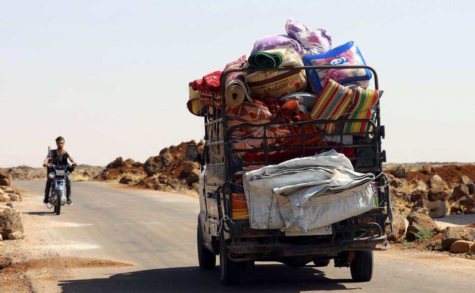 Plus de 12'000 Syriens ont fui au cours des trois derniers jours la province de Deraa, chargeant tous leurs biens sur des véhicules comme celui-ci. [Alaa al-Faqir - Reuters]