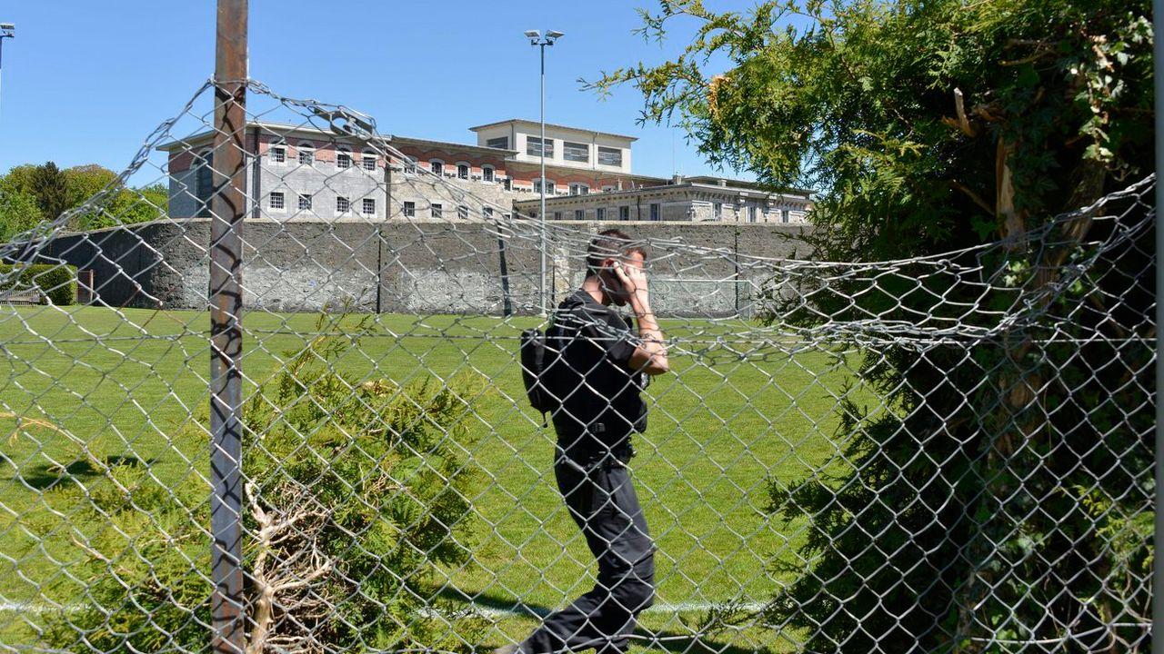 Un policier devant la prison lausannoise de Bois-Mermet, où a eu lieu une évasion en mai 2013. [Christian Brun - Keystone]