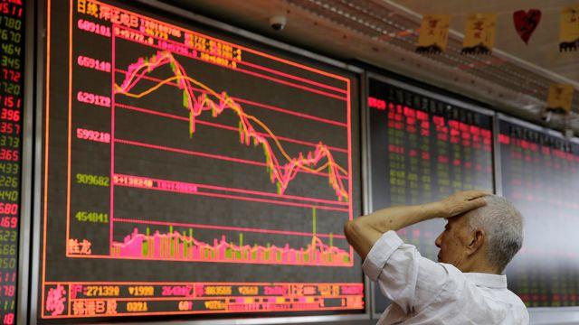 Un petit investisseur regarde la graphique de la bourse dans un bureau de courtage de Pékin. [Jason Lee - Reuters]