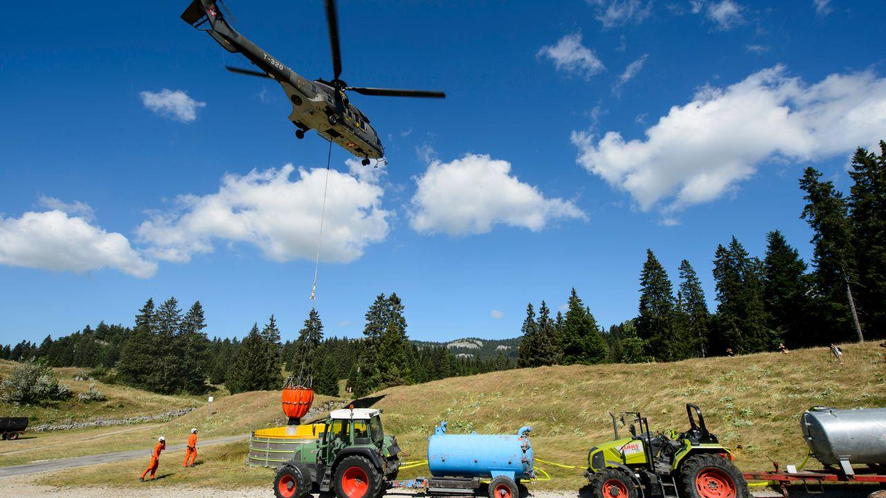 Un hélicoptère Super Puma de l'armée suisse apporte de l'eau dans un réservoir pour abreuver les vaches d'un paysan dans la région du Marchairuz. (image d'archives de la canicule de 2015) [Jean-Christophe Bott - Keystone]