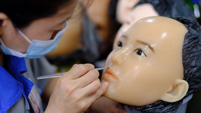 Une maquilleuse personnalise le visage d'une poupée selon la demande du client. [Michael Peuker - RTS]